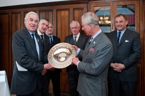 HRH The Prince of Wales receives the Royal Smithfield Club Bicentenary Trophy from John Coultrip (immediate past president of The Royal Smithfield Club). Behind – left to right:  John Campbell (past club chairman), Julian Hopwood (Club chairman elect), Rees Roberts (2011 Trophy winner) and Angus Stovold (Club chairman).