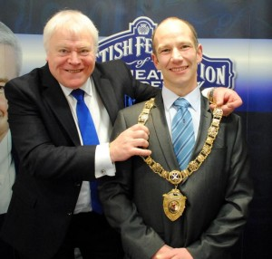 Past president Ian Faulds places the chain around the neck of new president Beaton Lindsay.