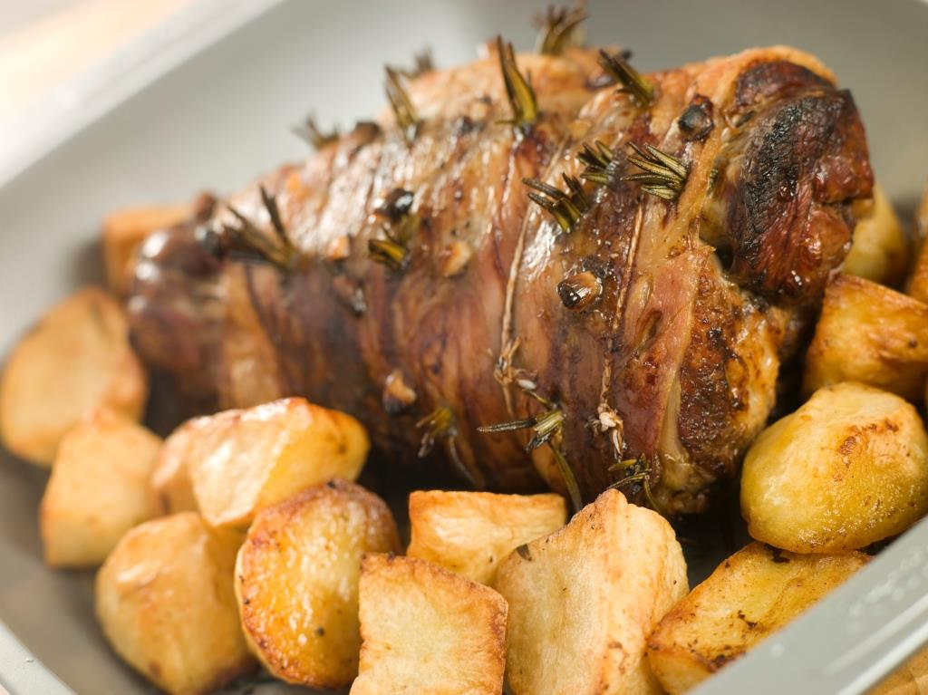 Roast leg of lamb studded with garlic and rosemary and roast potatoes.